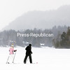 GABE DICKENS/ P-R PHOTO<br /> A pair of skiers gradually disappear into the swirling snow as they make their way across a frozen Mirror Lake in Lake Placid recently. Along with cross-country skiing, Mirror Lake is a popular destination for ice skating and pond hockey, fat tire biking, snowshoeing and other winter-related activities.