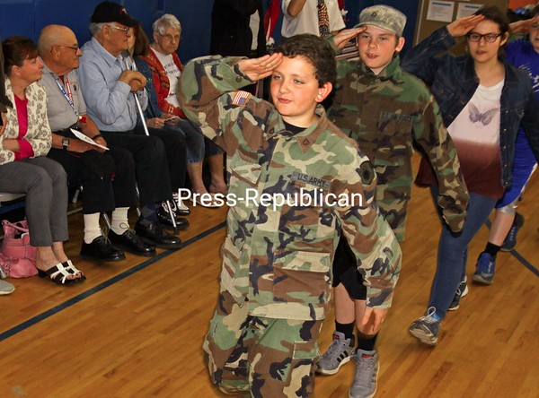 """ALVIN REINER/ P-R PHOTOS<br /> Kollin Christianson (from left), Shay LaFave and Jessie Mason honor guests at Ausable Valley Elementary School's annual Salute to Veterans as they march across the gym floor. Fifth- and sixth-graders, some dressed in the uniforms of family members, performed military demonstrations, gave patriotic readings, and, as they entered and left, saluted the 20 or so veterans there, who'd served in conflicts dating back to World War II. Organized by sixth-grade teacher and military veteran Marty Remillard, the event gave the students the chance to ask the vets about their service. Remillard also presented plaques to family members of four recently deceased veterans: Ralph Jarvis, Napoleon Light, Daniel Meegan and Albert Ston. """"Our kids learn best when they can see and experience things such as what freedom means,"""" Principal Ginene Mason said."""