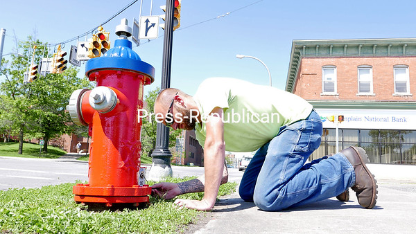 KAYLA BREEN/ STAFF PHOTO<br /> City of Plattsburgh Public Works worker Eric Desrocher finishes painting a fire hydrant at the corner of Cornelia and Margaret streets. Public Works plans to have all fire hydrants in the city repainted by the end of summer.