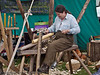 10 July 2011 Woodcraft fair 2011. Planing in action.<br /> A simple wooden vice holds the workpiece. The jaws are held shut by applying pressure with the feet.