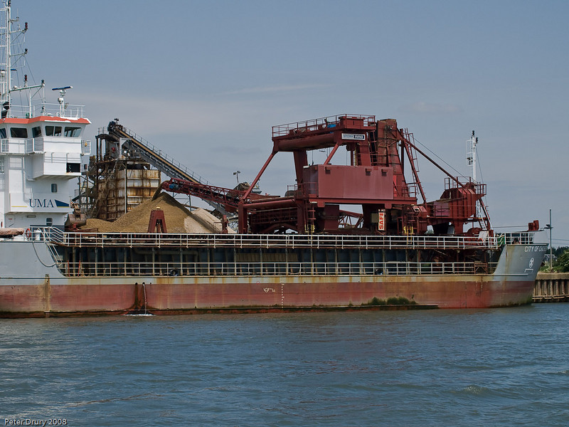 Aggregates Wharf unloading. Copyright Peter Drury 2010<br /> View of the coaster unloading material onto the wharf. The large structure on the ship contains a jawed scoop which brings up the material from the hold and dumps it in the hopper at the rear of the structure. The contents of the hopper are taken on a belt and deposited on the wharf.