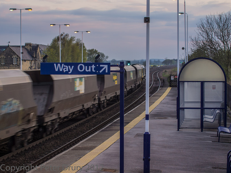 Taken from platform 1. A loaded coal train, hauled by a Class 66 diesel locomotive, heads north towards York. It probably originated from Gascoigne Wood on the Leeds Selby line. This train will have joined this route at Sherburn-in-Elmet, having taken the spur line at Gascoigne Wood.