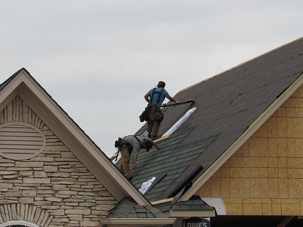 Staff photo by Cathy Spaulding<br /> Roofers work on a residential garage near Muskogee Country Club while storm clouds move in Monday afternoon. Heavy showers are expected today with periods of rain expected for the rest of the week, according to Muskogee's AccuWeather forecast.