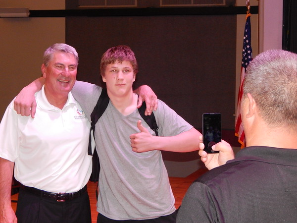 Staff photo by Mark Hughes<br /> Uwe von Schamann and Alice Robertson Junior High School student Samuel Brewer pose for a photo. Von Schamann gave a motivational presentation Tuesday afternoon to the seventh and eighth graders. Von Schamann was a place kicker for the University of Oklahoma and played for the Miami Dolphins for six years.