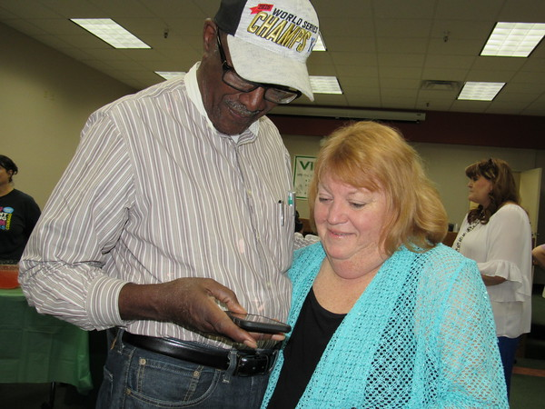 Staff photo by Cathy Spaulding<br /> Muskogee Public Schools Special Programs Director Deborah Winburn looks at smartphone pictures with former MPS administrator Cedric Johnson during a retirement reception Wednesday. Winburn is ending a 34-year career with the district.