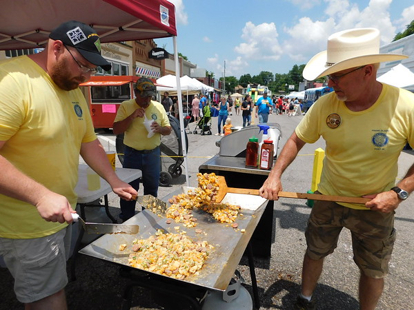 CATHY SPAULDING/Muskogee Phoenix<br /> Nathan Abel, left, and Clayton Armstrong stir okra on an outdoor griddle during the Fort Gibson Sweet Corn Festival. The succotash is a festival tradition that celebrates the harvest, Armstrong said.