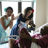 "Staff photo by Harrison Grimwood<br /> Pin-ups for Veterans models Gina Elise, left, and Valentina ""CiCi"" Cahill, right, flirt with Navy veteran Thello L. White during their visit to the Jack C. Montgomery VA Medical Center."