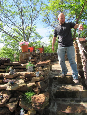 Staff photo by Cathy Spaulding<br /> Tyler Radick walks down the steps of a stone sitting area that he and his father built. The men flip houses for profit.