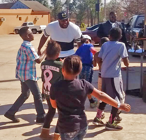 Staff photo by Mike Kays<br /> Muskogee High School graduate Robert Thomas, now a Miami Dolphins defensive lineman, dances with kids Saturday at a block party that he organized with another Rougher ex, Eddie Venters.