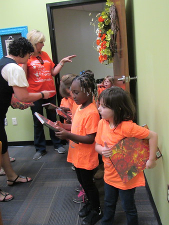 Staff photo by Cathy Spaulding<br /> Early Childhood Center pupils Malia Gaulden, center, and Grace Marder, right, hang onto big books while ECC Principal Malinda Lindsey hands out postcard packets. Artist Dale Chihuly sent books, postcards and T-shirts to the school after teachers sent him pictures of a project by the students.
