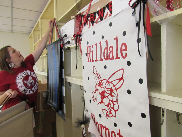 Staff photo by Cathy Spaulding<br /> Hilldale Elementary PTO President Ashley Ireland hangs banners painted by teachers. The banners will be auctioned Friday during the school's Hornet Night fundraiser.