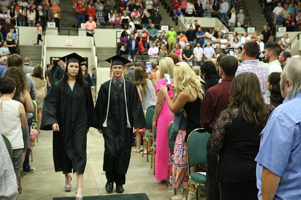 Staff photo by Harrison Grimwood<br /> Hilldale High School graduates enter the arena as they prepare to walk during the school's graduation ceremony Friday at the Muskogee Civic Center.