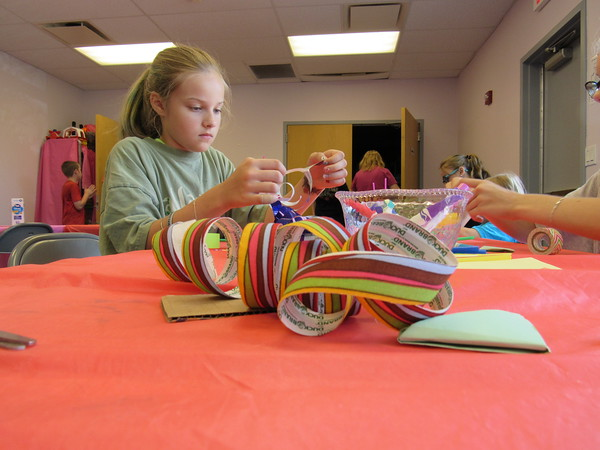 Staff photo by Cathy Spaulding<br /> Kaya Cox, 9, can choose from a variety of ribbons to decorate her straw field goal. She joins other youngsters each Thursday for a summer craft program.