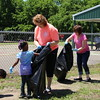 Staff photo by Harrison Grimwood<br /> Students at Muskogee Early Childhood Center pick up litter around their school Wednesday afternoon while classroom assistant Denise McEntyre holds the bag for what they find. McEntyre said teachers brought the students out for a belated Earth Day celebration, which they were unable to have in April because of inclement weather.