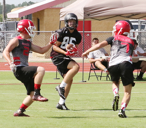 Phoenix special photo by John Hasler<br /> Hilldale's Alex Puckett catches a pass between Stigler defenders during the 7-on-7 football tournament Monday at Hilldale High School. Puckett and the Hornets won the event.
