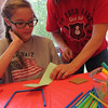 Staff photo by Cathy Spaulding<br /> Q.B. Boydstun Librarian Judy Walker, right, helps Araya Cox, 11, fold a paper football to go through a straw field goal during Thursday craft period at Q.B. Boydstun Library. The craft time runs through July 21.