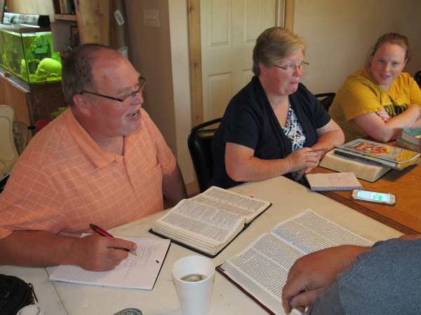 Staff photo by Cathy Spaulding<br /> Brushy Mountain Baptist Church bivocational pastor Mark Haile, left, leads a Bible study at a member's house along with his wife, Kim Haile, center, and daughter, Katie Haile.