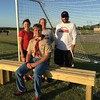 Special photo by Travis Sloat<br /> Matthew Burris sits on one of the benches he provided for young soccer players at Fort Gibson's Whitlock Sports Complex. With him are Chelsea Smith, left, Sherry Shropshire-Jennings, and Robert Hazelwood, all administrators of the Fort Gibson Recreational Soccer Club.
