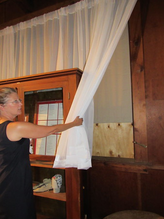 Staff photo by Cathy Spaulding<br /> Bacone College's executive director of development, Kimberly Gilliland, shows the boarded-over historic windows at Ataloa Lodge Museum. Bacone will play host Thursday for a reception intended to raise money for the restoration of the windows.