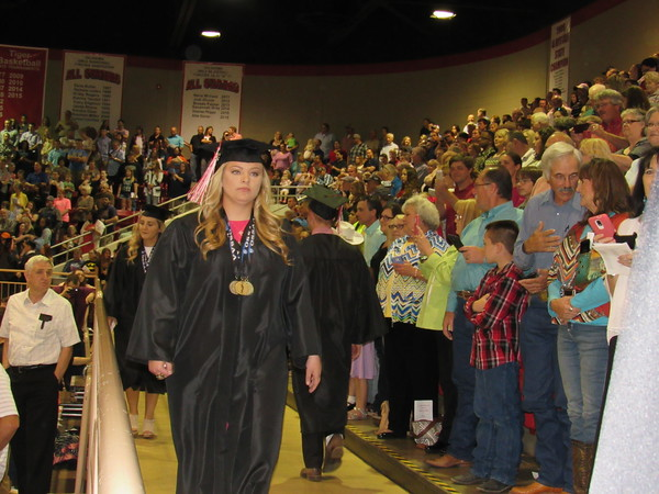 Staff photo by Cathy Spaulding<br /> Fort Gibson High School seniors pass each other during the pro- cessional for the Class of 2016 Commencement on Friday at Harrison Field House.