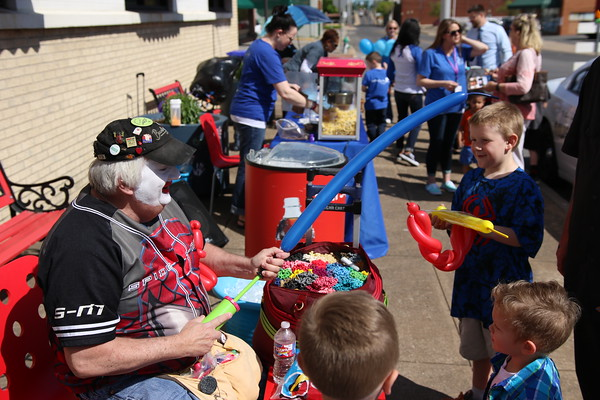 Staff photo by Harrison Grimwood<br /> Honky DaClown twists and folds balloons while a group of children watch during the Child Abuse Prevention Block Party on Thursday.