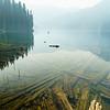 Smoky skies and long forgotten logs reflected in Lizzie Lake near Pemberton, British Columbia.