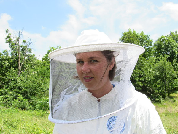 Elizabeth Callahan peers through the veil she must wear while tending her bee hives. She said she hopes to make honey for her family.