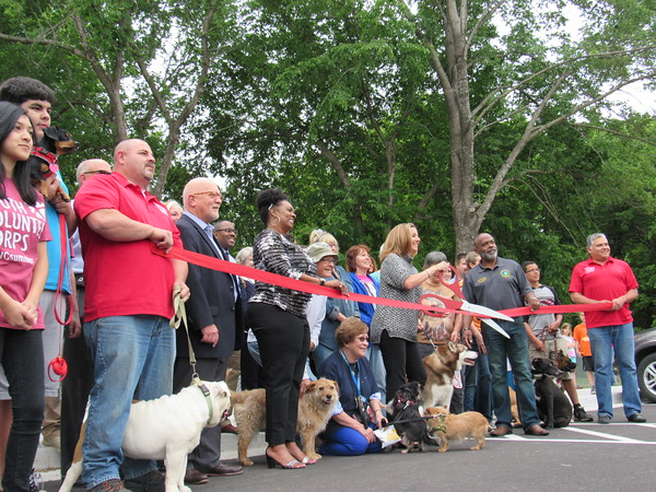 Staff photo by Cathy Spaulding<br /> Dogs and dog-lovers join city and business dignitaries Thursday for the grand opening of the Coody Creek Bark Park and Trail extension. The Bark Park, on south Main Street, features separate play areas for big dogs and small dogs. Each area features pooch-sized water fountains and agility equipment. The Coody Creek Trail extension is about eight-tenths of a mile long and connects with Centennial Trail, said Muskogee Parks and Recreation Director Mark Wilkerson.