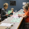 Staff photo by Harrison Grimwood<br /> Elaine Brownell, left, helps Betty Luttrell, right, and Nancy Hoffman prepare to vote Friday during the early voting period at the Muskogee County Election Board.