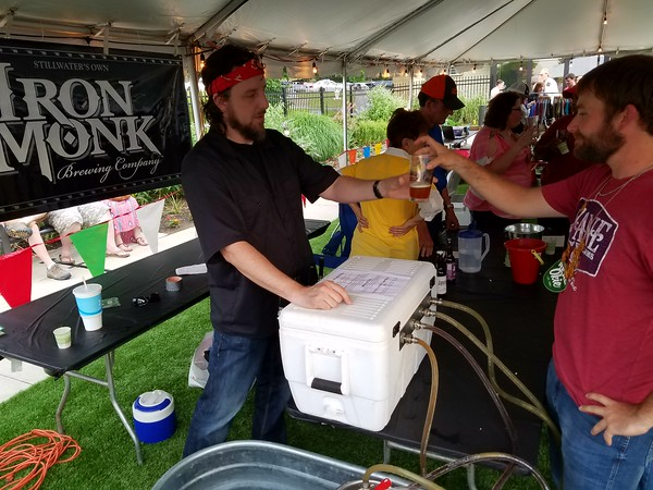 """Staff photo by Mark Hughes<br /> Dave Monk provides Brett Thompson one of his brewery's four varieties of beer during Friday evening's second annual Real Okie Craft Beer Fest at the butterfly Papilion at Honor Heights Park. """"This is the best (beer) festival this side of the state,"""" said Monk, who is a co-owner of Iron Monk Brewing Co. Around 500 tickets were sold for the event."""