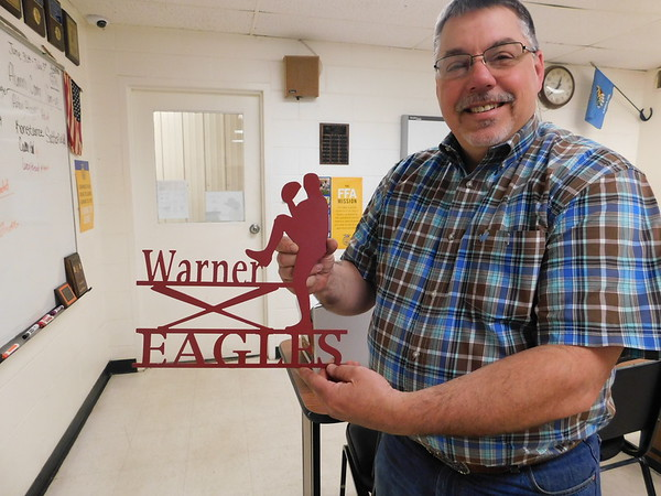 KENTON BROOKS/Muskogee Phoenix<br /> Warner High School's agriculture education teacher and FFA sponsor Ira Jackson proudly displays one of the designs his students made using a plasma cutter.