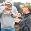 Derek Whitford, left, and Nakia Goad sample barbecue Saturday's 35th annual Exchange Club of Muskogee's Chili and Barbecue Cook-Off. The cold, rainy day didn't scare people, including Muskogee residents Whitford and Goad, away from the event.