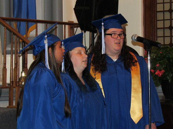 """Staff photo by Cathy Spaulding<br /> Oklahoma School for the Blind seniors, from left, Destiny Starr Tanyan, Allison Makayla Fetner and valedictorian Jennifer Joy Nicole Ratliff sing during Wednesday's commencement for the OSB Class of 2016. Eight members of the Oklahoma School for the Blind Class of 2016 graduated Wednesday. Salutatorian Logan James McCoy and valedictorian Ratliff gave speeches. News on 6 anchorman Craig Day told graduates """"often what people think of as overnight successes are people who put in years and years of hard work."""""""