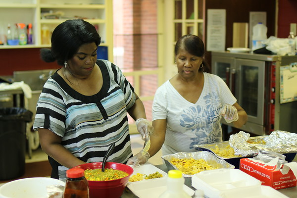 Staff photo by Harrison Grimwood<br /> Debbie Williams, left, and Erma Hardridge dish out mixed vegetables for fried fish meals, served as a fundraiser for Antioch Baptist Church's  youth ministries.