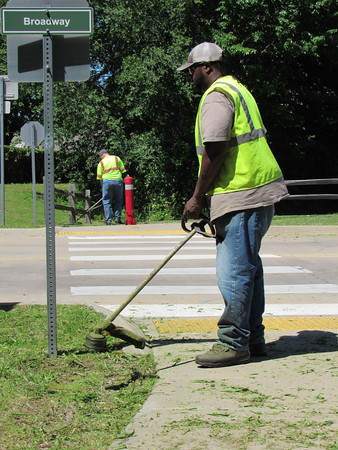 Staff photo by Cathy Spaulding<br /> Muskogee Parks and Recreation workers James Shook, left, and Tim- othy Moore cut weeds along Centennial Trail at the Broadway crossing Wednesday afternoon. Department director Mark Wilkerson said the entire trail — about seven miles in length — would be mowed, as would a mile-long spur trail from Centennial to South Main Street.
