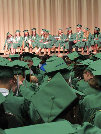 Staff photo by Cathy Spaulding<br /> Honored Muskogee High School seniors on the Muskogee Civic Center stage wait while classmates form a sea of green during commencement.