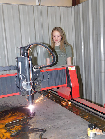 Warner High School junior Callee Good oversees the school's plasma cutter that cuts out shapes and designs into mild steel plates. Good and other FFA students made name plates for the school's Board of Education.