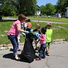 Staff photo by Harrison Grimwood<br /> Early Childhood Center teacher Lori Alexander works with children Wednesday to pick up litter around the grounds. The activity was a belated celebration of Earth Day, which is in April.