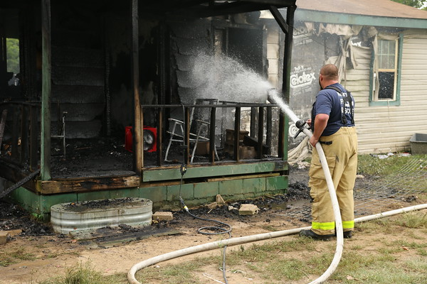 Staff photo by Harrison Grimwood<br /> Keefeton Volunteer Fire Department firefighters extinguish a residential fire shortly after 2 p.m. Tuesday in the 4000 block of East 133rd Street South. Firefighter Brandon Drake said the porch, living room and back door were involved when they arrived. The house was empty; neighbors told firefighters that the residents had moved out just the day before.