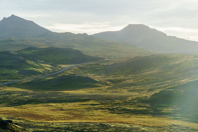 A car drives a dirt road north of Reykjavik, Iceland.