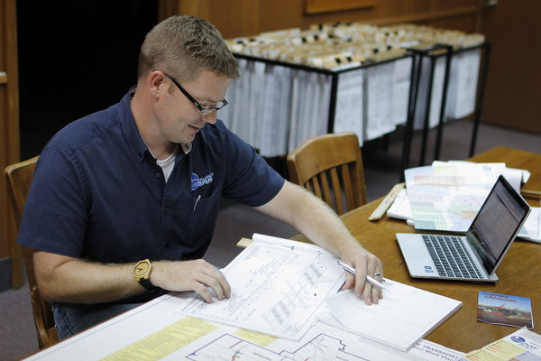 Staff photo by Harrison Grimwood<br /> Chris Wallace, a construction engineer for the Oklahoma Department of Transportation, reviews project plans for bridge rehabilitation during the 2016 summer season.