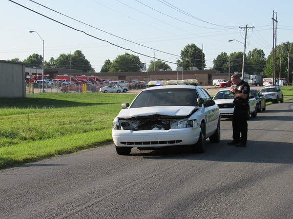 Staff photo by Cathy Spaulding<br /> A Muskogee Police officer examines a police cruiser involved in a three-vehicle collision Sunday afternoon on South 24th Street.