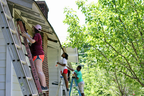 Staff photo by Harrison Grimwood<br /> Muskogee youths paint a house on North J Street on Tuesday afternoon. The youths and more than 50 of their peers divided into five teams to go out painting homes for a ministry project. Three churches participated.