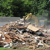Staff photo by Cathy Spaulding<br /> A trackhoe scrapes through remains of an old Bacone College faculty house. Vacant faculty houses are being demolished as part of Bacone's strategic plan to upgrade the campus.