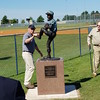 "Staff photo by Mark Hughes<br /> Mark Wilkerson, the director of Muskogee Parks and Recreation, rubs the foot of the statue of Robert Lee ""Bobby"" Sallie on his way to talk to Marshall Wade. The statue was unveiled Tuesday at Love-Hatbox Sports Complex. Sallie died in 1955 from a line drive to his temple. The Wade family paid for the statue."