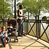Staff photo by Harrison Grimwood<br /> Andre Anderson fishes Thursday afternoon in the pond at Spaulding Park. He caught and released several fish while with two of his children, Daryion Anderson, 2, and Danielle Anderson, 1. Anderson said he saw worms in the dirt at his mother's home and decided fishing with his children would be a good way to unwind after work.
