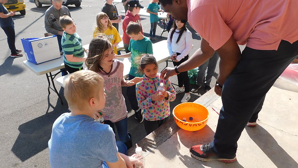 KENTON BROOKS/Muskogee Phoenix<br /> Muskogee Public Library's Daniel Swanson hands out plastic bottles to, from left, John Cook, Lanee Cartwright and Sarin Harjo during the survival class held Tuesday at the library. A group of 28 students and adults learned how a CD and a combination of a plastic bottle, gravel, charcoal and cotton balls can help someone survive in the wilderness. Josiah Parrish, a self-described hobbyist-survivalist, taught the class.