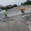 Staff photo by Cathy Spaulding<br /> Logos Construction workers jackhammer out part of the Oklahoma 16 bridge across the Arkansas River on Monday. Traffic across the river is restricted to one lane during repair and maintenance on the bridge. Chris Wallace, an Oklahoma Department of Transportation construction engineer, said the work should continue until early May.