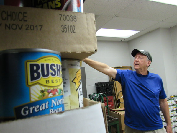 Staff photo by Cathy Spaulding<br /> Carment arranges donations inside<br /> a store- room for Muskogee Community Pantry. It operates out of First United Methodist Church.