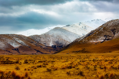 Extreme arid tundra terrain at the base of the snow dusted foothills of the Southern Alps